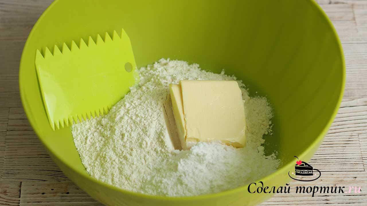 В миску высыпаем просеянную муку, сахарную пудру и сливочное масло комнатной температуры.