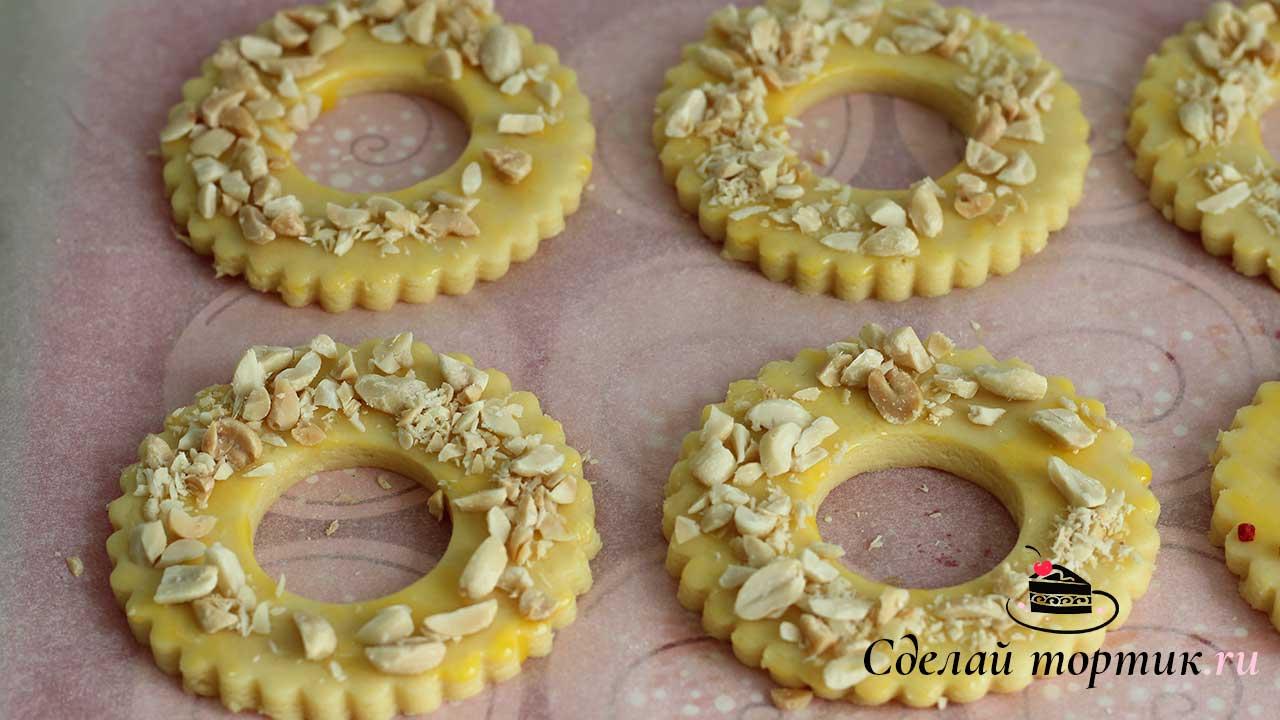 Выкладываем кольца на пергамент, сверху обмазываем желтком и посыпаем арахисом.